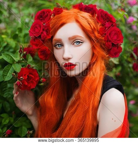 Portrait Of Young Unusual Pale Girl With Red Hair In Rose Garden. Beautiful Redhead Woman With Haird