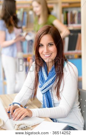 Female brunette student at high school library working on laptop