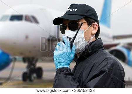 Security Guard Talking On Walkie Talkie Near Airplane