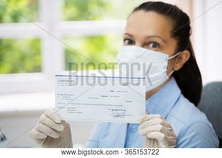 Woman In Face Mask Holding Paycheck Or Stimulus Check