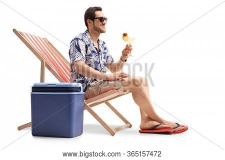 Happy man sitting on a deck chair and sipping a coctail with a cooling box beside isolated on white background