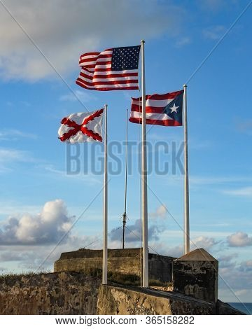 The Three Flags That Fly At El Morro In Old San Juan, Puerto Rico. American, Puerto Rican And Cross