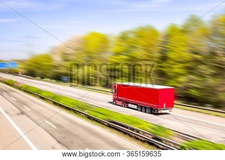 Truck Moves On The Road At Speed, Delivery Of Goods. Truck At Dawn Sun, Flashes Down The Road