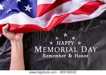 Happy Memorial Day. Man's Hand Hold American Flags With The Text Remember & Honor Against A Blackboa