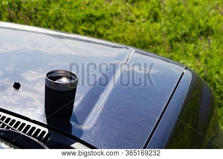 A Mug With Tea Stands On The Soot Of An Suv In The Middle Of A Green Meadow In Summer. A Cup Of Tea