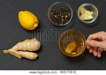 Health Remedy Foods For Cold And Flu Relief. Female Hands With A Cup Of Tea And Lemon, Ginger On A B