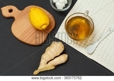 Health Remedy Foods For Cold And Flu Relief. Cup Of Tea, Lemon, Ginger On A Black Background. Top Vi