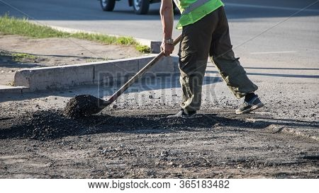 Workers Repair The Road Surface And Asphalt The Street. People In Overalls With Shovels Throw Dirt A