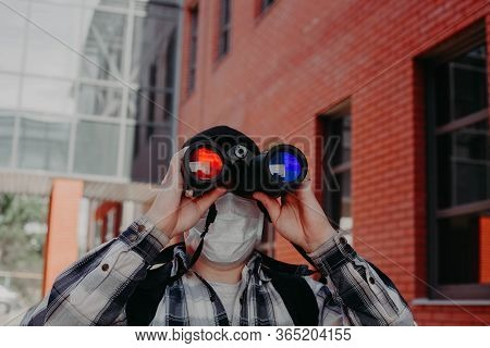 A Guy Looks Through Binoculars With Different Glasses In The Center Of The City
