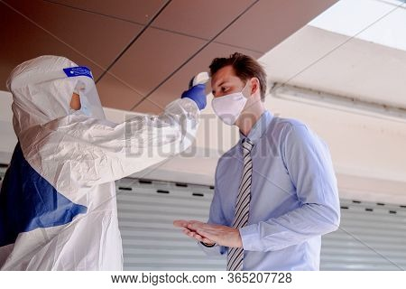 Social Distance Concept. Officer Wearing A Respirator Mask To Use Infrared Forehead Thermometer To C