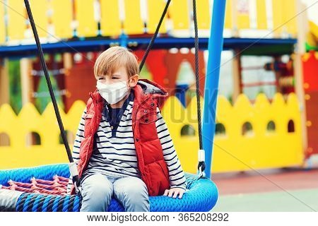 Sad Boy In Face Mask Playing Outdoors. Bored Child At Empty Playground Outside. Coronavirus Quaranti
