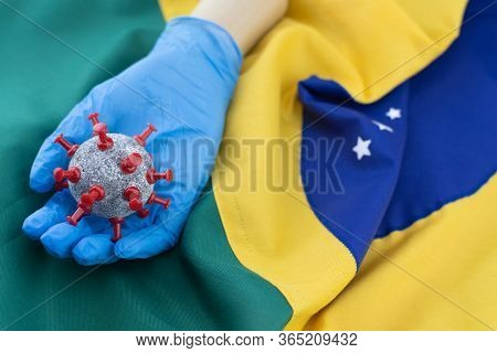 Wooden Hands Model Wearing Blue Gloves And Holding Ball Similar To Coronavirus Cells And Mask