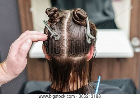 Hair Stylists Hand Divide Women Hair In Sections With Clips At Hair Salon. Hair Extension In A Profe