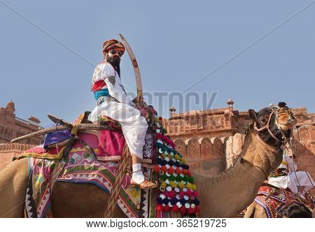 Bikaner, Rajasthan State, India - January 11, 2020: Indian Rajasthani Man With Sword Rriding On Came