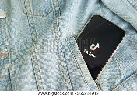 Tver, Russia-may 7, 2020, The Tik Tok Logo On A Smartphone Screen Sticks Out Of The Pocket Of A Deni