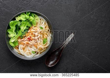 Guay Tiew Gai Cheek Or Thai Chicken Noodle Soup In Black Bowl On Dark Slate Backdrop. Guay Tiew Gai