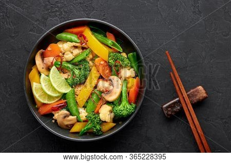 Pad Pak Ruam Or Veg Thai Stir-fried Vegetables In Black Bowl On Dark Slate Backdrop. Pad Pak Is Thai