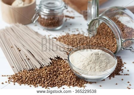 On A Wooden Table Lies A Glass Jar Of Buckwheat, On A White Wooden Table Are Scattered Buckwheat Gra