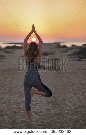 Young Sporty Fit Woman Is Doing Hatha Yoga Asana Vrikshasana Tree Pose On Beach On Sunset, Yoga Outd