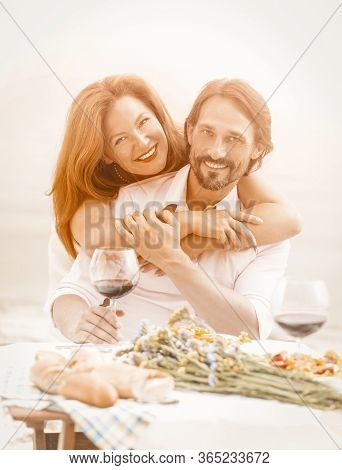 Beautiful Couple Resting Outdoors, Happy Woman Hugging Her Man. Man And A Woman Eat And Drink Wine I