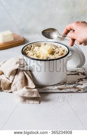 Old Fashioned Rolled Oat Porridge With Melting Butter In A Sauce Pan, A Hand Stirring, Copy Space Fo