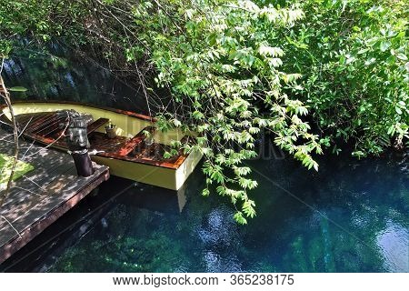 A Small Boat Awaits Lovers At A Wooden Pier. In The Clear Aquamarine Water Of The River, Overhanging