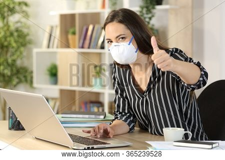 Happy Freelance Woman With Thumbs Up Working Avoiding Covid-19 With Mask Sitting On A Desk At Homeof