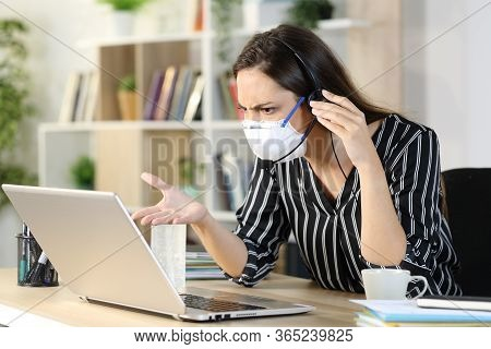 Angry Telemarketer Woman Checking Laptop While Calling Avoiding Coronavirus Sitting On A Desk At Hom