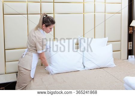 The Maid Adjusts The Pillows On The Bed. Cleaning In The Hotel Room. Photo In The Interior.