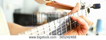 Man Plays Guitar, Male Hand Holds Neck Guitar. String Makes Beautiful Sound. Musician Tunes Guitar.