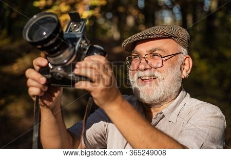 Old Photographer Look In Vintage Camera Outdoors. Photographer With Retro Camera. Reporter Or Journa