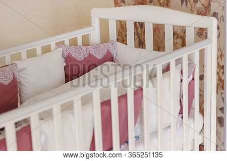 Baby Bed Crib With White And Burgundy Color Pillows With Laces