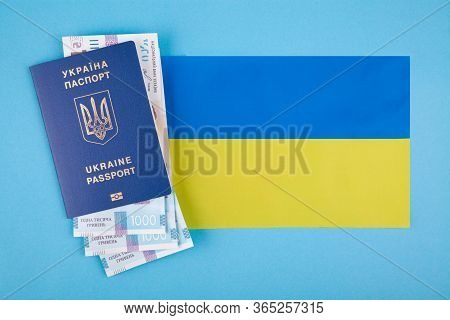 Ukrainian Passport, Banknotes And Flag On A Blue Background. The Concept Of Accumulation On Vacation