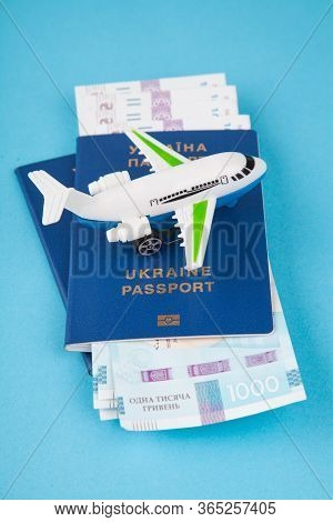 Two Ukrainian Passports, Banknotes And A Small Plane On A Blue Paper Background. The Concept Of Accu