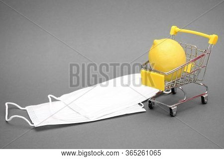 Lemon In A Shopping Cart And White Medical Masks On A Grey Background. Health And Vitamin Therapy. P