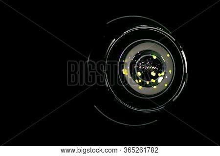Lense Flare Lights On Shutter. Reflection On Photo, Video Camera On Black Background. Sunlight Abstr