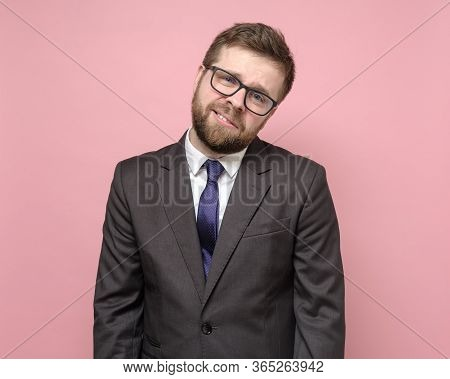 Tired Bearded Caucasian Man With Glasses And A Suit Smiles Mockingly And Looks At The Camera With In