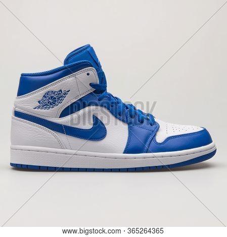 Vienna, Austria - June 14, 2018: Nike Air Jordan 1 Mid Blue And White Sneaker On White Background.
