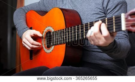 Girl Playing An Orange Acoustic Guitar Grips The Chord On The Fretboard. Musical Instrument Lesson C