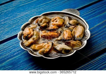 Pickled Mussels In Oil And Greens Photographed On A Blue Painted Wooden Surface.