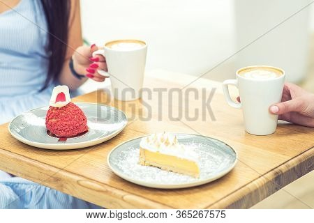 Two Young Women Meet At The Bar For Cappuccino With Desserts And To Chat. Two Women Having Snack In