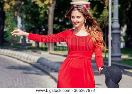 Smiling Adult Girl In Red Dress Is Catching Taxi On The City Street. Young Tourist Woman In Red Dres
