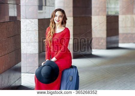 Tourist Adult Girl Is Sitting On A Suitcase And Looking At Camera. Tourist Young Woman Is Sitting On