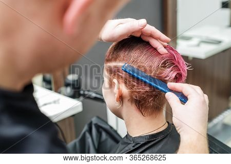 The Hairdresser Is Using Comb For Female Pink Hair In Hair Salon. Male Hand Is Combing Woman Short P