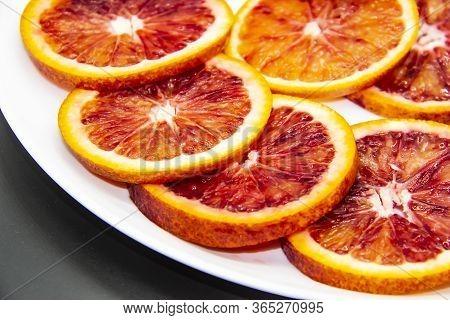 Sicilian Sliced orange On A White Plate On A Dark Background. Sliced Ripe Sicilian Oranges Against
