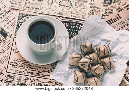 Old Yellowed Newspapers With News And Announcements Are Laid Out On The Table. Cup Of Coffee And Waf