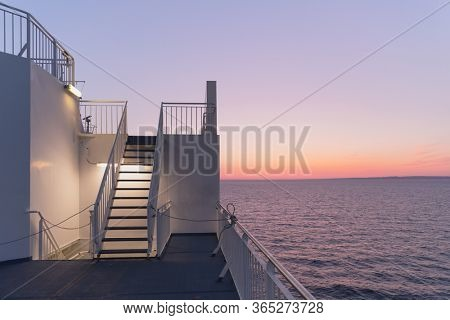 Deck of a cruise ship during sunset. Calm ocean and clear pink sky in evening time. Cruise vacations background. Minimalism in photography