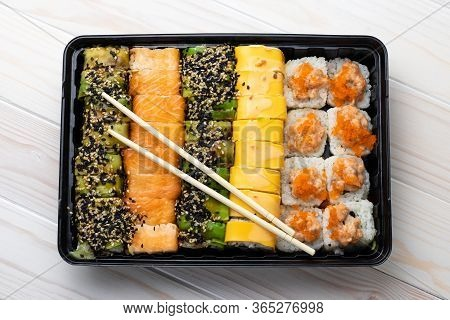 Set Of Sushi Rolls With Salmon And Vegetables In Black Tray And Wooden Chopsticks On Boards. Asian D