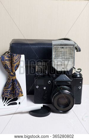 Photographer Accessories. Camera And Flash. Nearby Is A Bow Tie And A Notebook With A Pen. On A Ligh
