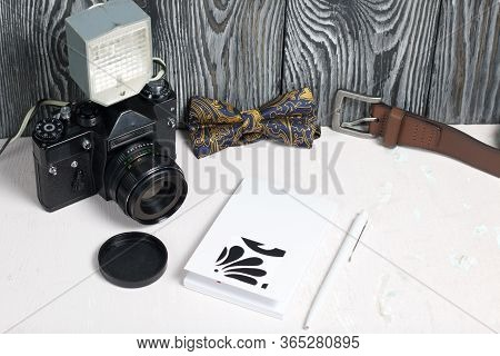 Photographer Accessories. Camera And Flash. Nearby Is A Bow Tie, Belt And Notebook With Pen. Against